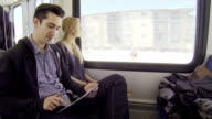 Young adult couple ride a train and play on tablet
