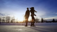Young adult couple skating together on ice.