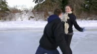 Young adult couple skating together on the ice..