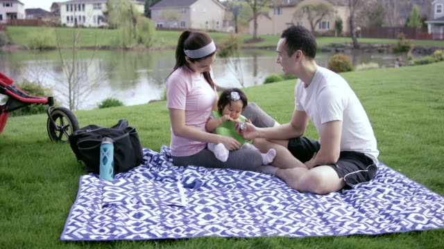 Young adult family eating in park