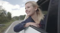 Young adult female hanging out of car window enjoying fresh air