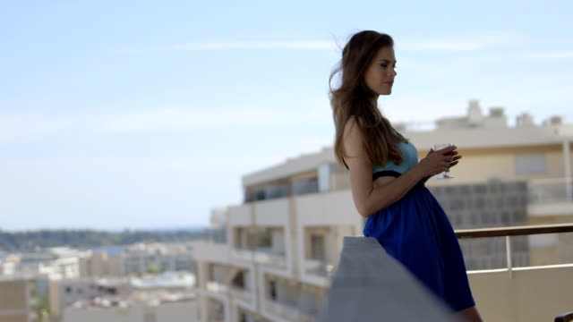 Young adult female on balcony in blue summer dress