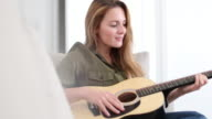 Young adult female playing acoustic guitar