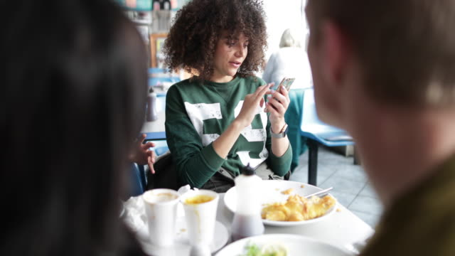 Young adult female showing friends photo on smartphone