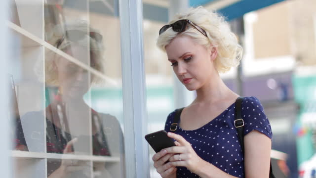 Young adult female using a smartphone whilst shopping