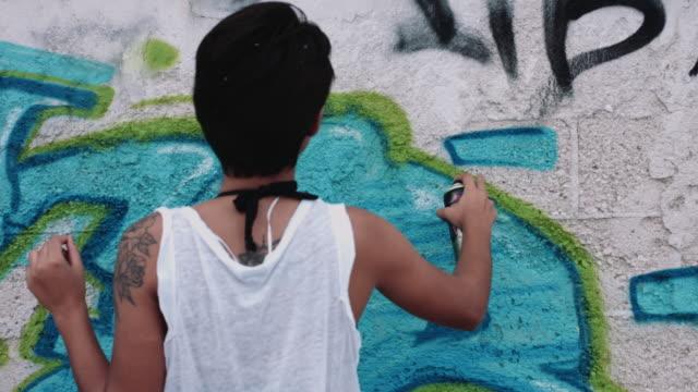 Young adult friend making graffiti on urban wall