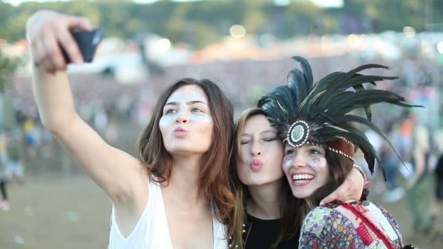 Young adult friends taking selfie at music festival