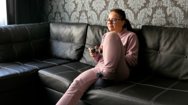 Young adult girl playing video games on the couch