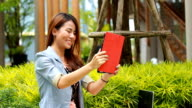 Young adult girl sitting on a bench outdoors and using a tablet facetime
