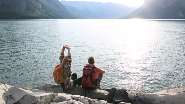 Young adult hikers relax at edge of mountain lake