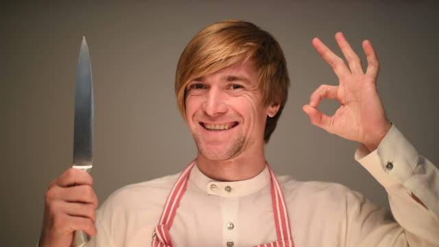 Jungen Erwachsenen männlichen chef lächelnd und zeigt OK auf einem grauen Hintergrund
