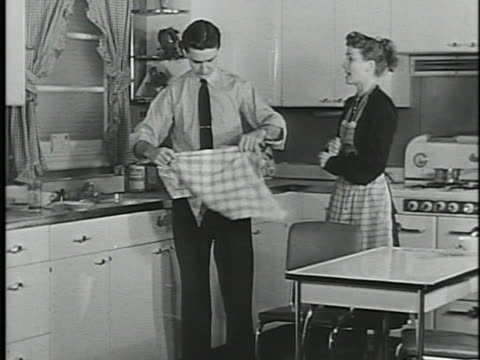 Young adult male female standing in eatin kitchen w/ metal table FG male placing dish towel into belt preparing to wash dishes female tying apron at...