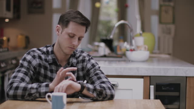 Young Adult male using smart watch at home on kitchen table