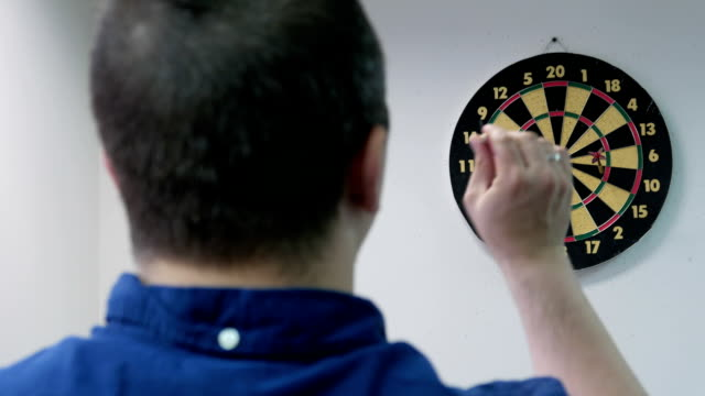 Young adult man playing darts in the office