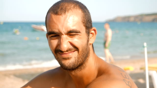 Young adult man sitting on the beach and looking at camera