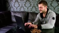 Young adult man sitting on the couch and working on a laptop at home