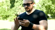 Young adult man using his smart phone outdoors