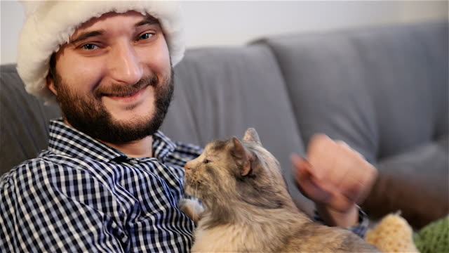 young adult man  with  cat look to camera