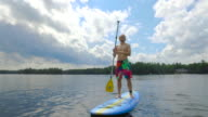 Young adult paddle boarding outdoors during summer