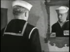 Young adult US Navy sailor putting on cap in front of mirror saluting 'Aye Aye Sir' WS Soldiers in uniform piling duffel bags in stack at train...