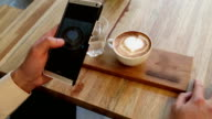 Young adult using smart phone for capture his coffee