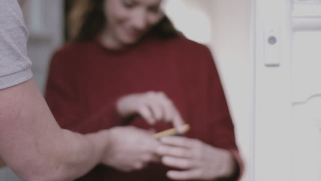 Young adult Woman signing for parcel at home