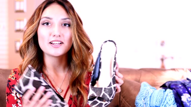Young adult woman vlogging about fashionable clothes and shoes.