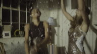 Young adult women dancing at party with confetti