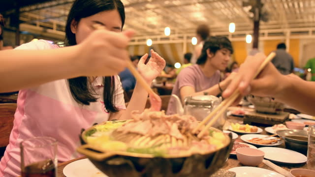 A young adults is happy for eating buffet with her friends.