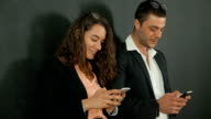 Young adults male and female flirting and texting using their smart phones