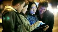 Giovani adulti divertirsi con tablet in città di notte