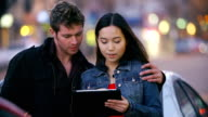 Young adults play with tablet in big city at night