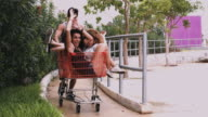 Young adults playing with shopping trolley