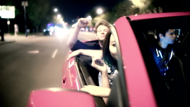 Young adults ride in a convertible during summer