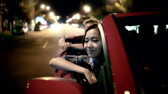 Young adults ride in a convertible on summer night