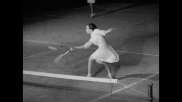 NIGHT Young adults walking toward clubhouse VS Young woman in tennis skirt male in shorts BG playing Doubles tennis game on court