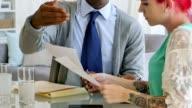 Ung afrikansk Amerikan affärsman diskuterar något med kvinnlig kollega