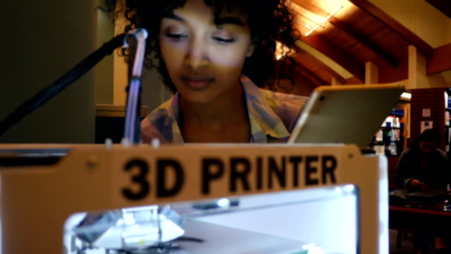 Young African American college student uses digital tablet to program 3D printer
