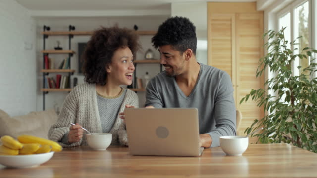 Young African american couple having fun while surfing the net on laptop at home.