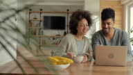 Young African American couple having fun while surfing the net on laptop.