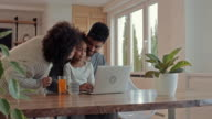 Young African American family enjoying while using laptop together at home.