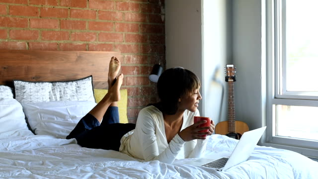 Young African American Frauen im Bett mit Kaffee und Laptop