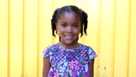 Young African American girl smiling and looking serious