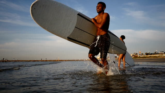 Young African American male surfer runs into the water with surfboard