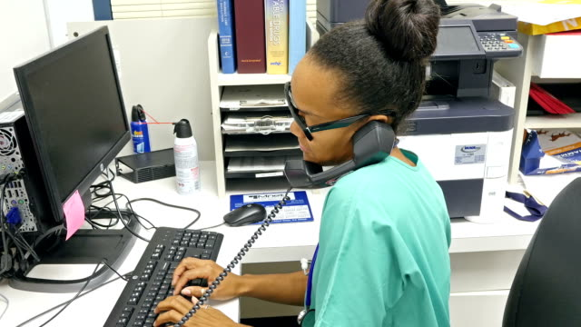 Young African American nurse at nurses' station answering phone