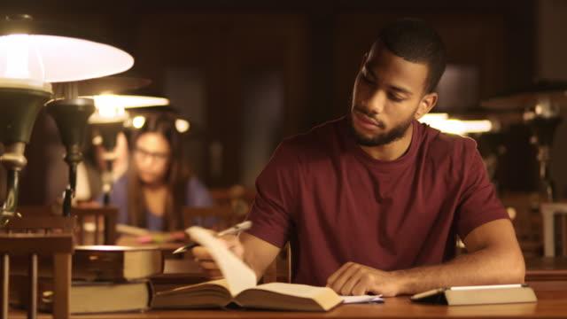 DS ung afroamerikansk man studera i biblioteket