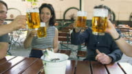 DS MS young and mature couple sitting at table in beer garden engaged in conversation, raising their beer mugs and toasting each other
