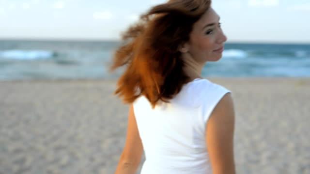 Giovane e attraente donna in tramite ealking sulla spiaggia e godersi il tramonto mi