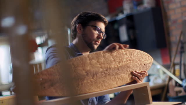 Young artisan polishes wooden skateboard with cloth in workshop