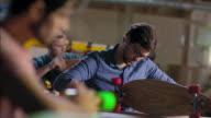 Young artisans assemble longboard kits in modern wood shop